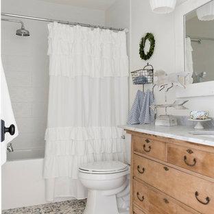 Diseño de cuarto de baño infantil, campestre, con paredes blancas, armarios tipo mueble, puertas de armario de madera oscura, bañera empotrada, combinación de ducha y bañera, baldosas y/o azulejos blancos, lavabo bajoencimera, suelo multicolor, ducha con cortina y encimeras blancas