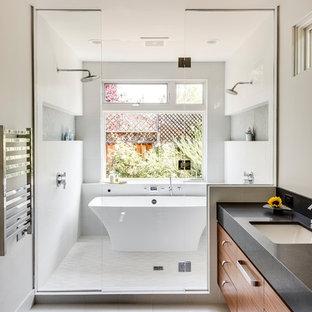 Cette image montre une grand salle de bain principale design avec un placard à porte plane, des portes de placard en bois brun, une baignoire indépendante, un mur blanc, un sol en carrelage de céramique, un espace douche bain, un lavabo encastré, une cabine de douche à porte battante, un plan de toilette en quartz modifié, un sol gris et un plan de toilette noir.