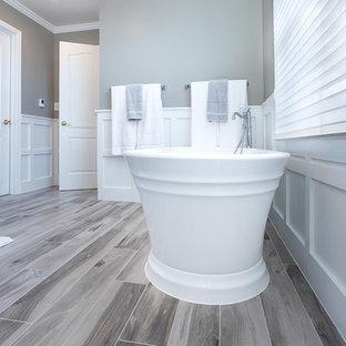 Foto de cuarto de baño principal, minimalista, grande, con armarios con paneles empotrados, puertas de armario blancas, bañera exenta, ducha abierta, sanitario de una pieza, baldosas y/o azulejos blancos, baldosas y/o azulejos de mármol, paredes grises, suelo de baldosas de porcelana, lavabo bajoencimera, encimera de cuarzo compacto, suelo gris, ducha con puerta con bisagras y encimeras blancas