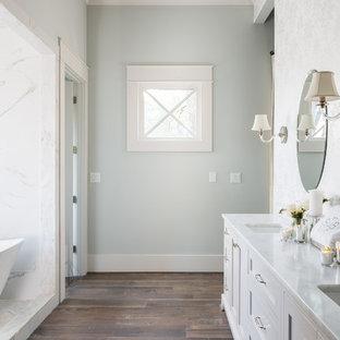 Aménagement d'une grand salle de bain principale campagne avec un placard avec porte à panneau encastré, des portes de placard grises, un bain japonais, un espace douche bain, un carrelage blanc, du carrelage en marbre, un mur bleu, un sol en bois brun, un lavabo encastré, un plan de toilette en marbre et aucune cabine.