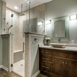 Modelo de cuarto de baño principal, rústico, de tamaño medio, con armarios con paneles lisos, puertas de armario de madera oscura, ducha esquinera, baldosas y/o azulejos beige, baldosas y/o azulejos de travertino, paredes beige, suelo de madera en tonos medios, lavabo sobreencimera y encimera de granito