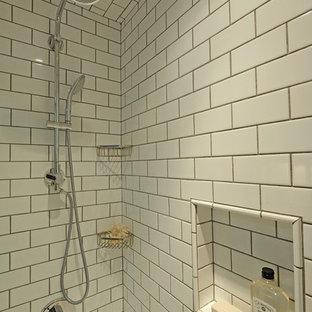 Inredning av ett klassiskt litet badrum, med skåp i mellenmörkt trä, vit kakel, vita väggar, ett undermonterad handfat, skåp i shakerstil, marmorbänkskiva, ett badkar i en alkov, en toalettstol med hel cisternkåpa, tunnelbanekakel, klinkergolv i keramik och en dusch/badkar-kombination