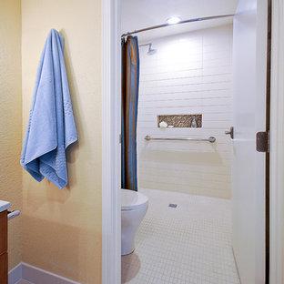 Idéer för att renovera ett mellanstort funkis en-suite badrum, med släta luckor, skåp i mellenmörkt trä, en kantlös dusch, en toalettstol med hel cisternkåpa, vit kakel, gula väggar, klinkergolv i porslin, ett badkar i en alkov, tunnelbanekakel, ett undermonterad handfat och bänkskiva i kvarts