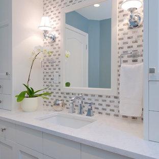 バンクーバーの広いトランジショナルスタイルのおしゃれなマスターバスルーム (アンダーカウンター洗面器、シェーカースタイル扉のキャビネット、珪岩の洗面台、アルコーブ型浴槽、オープン型シャワー、一体型トイレ、青い壁、セラミックタイルの床、白いキャビネット、グレーのタイル、白いタイル) の写真