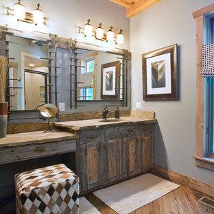 Ejemplo de cuarto de baño principal, rural, de tamaño medio, con armarios estilo shaker, puertas de armario con efecto envejecido, paredes azules, suelo de madera clara, lavabo integrado y encimera de piedra caliza