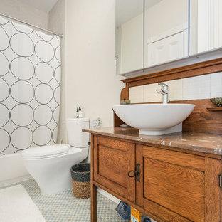 Imagen de cuarto de baño clásico renovado con armarios tipo mueble, puertas de armario de madera oscura, bañera empotrada, combinación de ducha y bañera, paredes beige, lavabo sobreencimera, encimera de madera, suelo gris, ducha con cortina y encimeras marrones