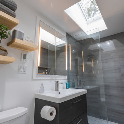 Small trendy master gray tile and porcelain tile ceramic tile and gray floor doorless shower photo with flat-panel cabinets, brown cabinets, a two-piece toilet, white walls, a drop-in sink and a hinged shower door