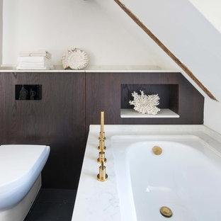 Kleines Modernes Badezimmer mit flächenbündigen Schrankfronten, braunen Schränken, Eckbadewanne, Wandtoilette, weißer Wandfarbe, schwarzem Boden und weißer Waschtischplatte in Sussex