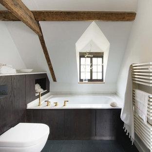 Idée de décoration pour une petite salle de bain design avec un placard à porte plane, des portes de placard marrons, une baignoire d'angle, un WC suspendu, un mur blanc, un sol noir et un plan de toilette blanc.