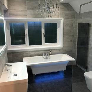 Ispirazione per una grande stanza da bagno per bambini minimal con vasca freestanding, doccia aperta, WC a due pezzi, piastrelle grigie, piastrelle in ceramica, pareti grigie, pavimento in mattoni e lavabo a consolle