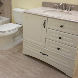 Inspiration for a small traditional 3/4 bathroom in Denver with raised-panel cabinets, white cabinets, an alcove tub, a shower/bathtub combo, a two-piece toilet, yellow walls, laminate floors, an undermount sink, granite benchtops, beige floor and a shower curtain.