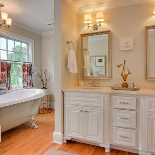 アトランタのトラディショナルスタイルのおしゃれな浴室 (レイズドパネル扉のキャビネット、白いキャビネット、猫足バスタブ、ベージュの壁、無垢フローリング、アンダーカウンター洗面器、茶色い床、ベージュのカウンター、洗面台2つ) の写真