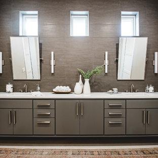 Esempio di una stanza da bagno padronale contemporanea di medie dimensioni con ante lisce, ante grigie, piastrelle marroni, pareti grigie, lavabo sottopiano, piastrelle in pietra, pavimento in travertino e top bianco