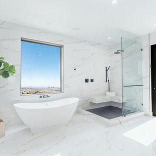 Foto på ett mycket stort 60 tals vit en-suite badrum, med ett fristående badkar, en hörndusch, vitt golv, vit kakel, vita väggar, med dusch som är öppen och marmorgolv