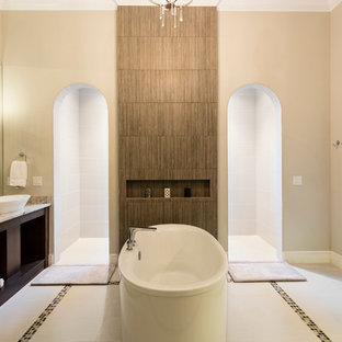 Foto de cuarto de baño principal, actual, grande, con armarios estilo shaker, puertas de armario de madera en tonos medios, baldosas y/o azulejos beige, paredes beige, lavabo sobreencimera, bañera exenta, ducha a ras de suelo y ducha abierta