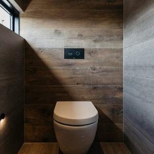 アデレードの大きいコンテンポラリースタイルのおしゃれなバスルーム (浴槽なし) (家具調キャビネット、淡色木目調キャビネット、コーナー設置型シャワー、グレーのタイル、グレーの壁、磁器タイルの床、一体型トイレ、磁器タイル、タイルの洗面台、茶色い床、オープンシャワー、ブラウンの洗面カウンター) の写真