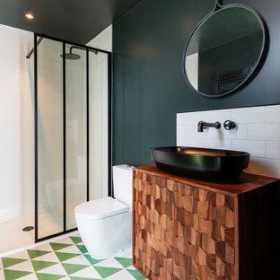 Design ideas for a contemporary shower room bathroom in Devon with freestanding cabinets, medium wood cabinets, an alcove shower, a two-piece toilet, white tiles, metro tiles, green walls, a vessel sink, wooden worktops, multi-coloured floors and brown worktops.