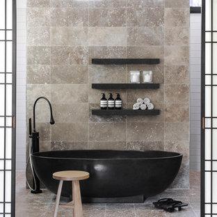 Aménagement d'une salle de bain contemporaine avec une baignoire indépendante, un carrelage beige, un sol beige et du carrelage en travertin.