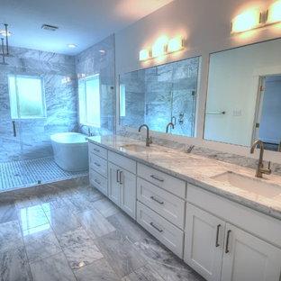 Foto de cuarto de baño principal, actual, grande, con encimera de mármol, bañera exenta, ducha abierta, baldosas y/o azulejos blancos y suelo de mármol