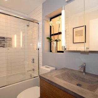 Kleines Modernes Duschbad mit flächenbündigen Schrankfronten, hellbraunen Holzschränken, Badewanne in Nische, Duschbadewanne, Wandtoilette mit Spülkasten, weißen Fliesen, grauer Wandfarbe, integriertem Waschbecken, Beton-Waschbecken/Waschtisch, Schiebetür-Duschabtrennung und grauer Waschtischplatte in San Francisco