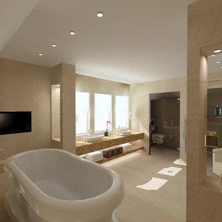 Modelo de cuarto de baño de estilo americano, de tamaño medio, con lavabo con pedestal, encimera de mármol, bañera exenta, sanitario de pared, baldosas y/o azulejos beige, baldosas y/o azulejos de cerámica, paredes beige y suelo de baldosas de cerámica