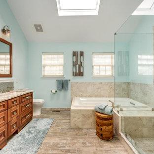 Ispirazione per una stanza da bagno padronale minimalista di medie dimensioni con ante a filo, ante marroni, piastrelle blu, top in quarzo composito, top beige, vasca da incasso, doccia ad angolo, WC a due pezzi, piastrelle di vetro, pareti blu, pavimento in gres porcellanato, lavabo sottopiano, pavimento beige e porta doccia a battente