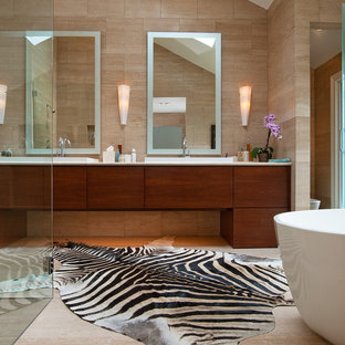 Example of a large minimalist master beige tile and porcelain tile porcelain tile bathroom design in Atlanta with flat-panel cabinets, dark wood cabinets, beige walls, a drop-in sink and limestone countertops