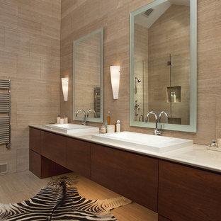 Ispirazione per una grande stanza da bagno padronale moderna con lavabo da incasso, ante lisce, piastrelle beige, ante in legno bruno, vasca freestanding, doccia ad angolo, piastrelle in ceramica, pareti beige, pavimento in gres porcellanato e top in pietra calcarea
