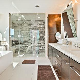 Создайте стильный интерьер: главная ванная комната среднего размера в современном стиле с плоскими фасадами, темными деревянными фасадами, отдельно стоящей ванной, душем в нише, коричневой плиткой, разноцветной плиткой, белой плиткой, удлиненной плиткой, белыми стенами, полом из керамической плитки, врезной раковиной, столешницей из гранита, душем с распашными дверями, белым полом и бежевой столешницей - последний тренд
