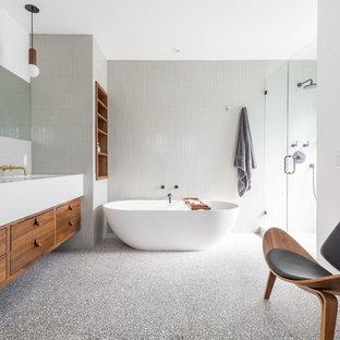 Пример оригинального дизайна интерьера: большая главная ванная комната в современном стиле с плоскими фасадами, отдельно стоящей ванной, душем в нише, унитазом-моноблоком, серой плиткой, керамической плиткой, белыми стенами, полом из терраццо, врезной раковиной, столешницей из искусственного кварца, серым полом, душем с распашными дверями, белой столешницей и фасадами цвета дерева среднего тона