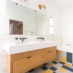 Drop-in bathtub - mid-sized contemporary white tile and ceramic tile cement tile floor and multicolored floor drop-in bathtub idea in Los Angeles with flat-panel cabinets, a one-piece toilet, white walls, an undermount sink, quartz countertops, white countertops and medium tone wood cabinets