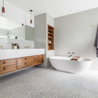Modern inredning av ett stort vit vitt en-suite badrum, med släta luckor, skåp i mörkt trä, ett fristående badkar, en dusch i en alkov, en toalettstol med hel cisternkåpa, grå kakel, keramikplattor, vita väggar, terrazzogolv, ett undermonterad handfat, bänkskiva i kvarts, grått golv och dusch med gångjärnsdörr