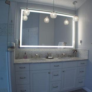 Inspiration för mellanstora klassiska flerfärgat en-suite badrum, med skåp i shakerstil, vita skåp, ett fristående badkar, en hörndusch, en toalettstol med hel cisternkåpa, vit kakel, keramikplattor, blå väggar, klinkergolv i porslin, ett undermonterad handfat, bänkskiva i kvarts, grått golv och dusch med gångjärnsdörr