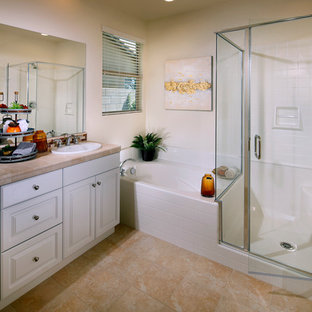 Example of a transitional master white tile beige floor bathroom design in Orange County with raised-panel cabinets, white cabinets, white walls, a drop-in sink, a hinged shower door and beige countertops