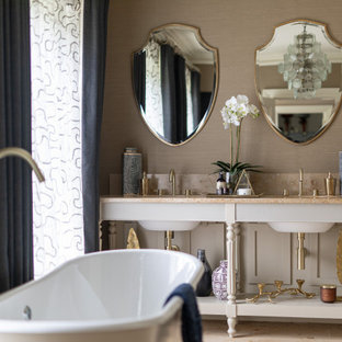 Inspiration for a medium sized classic ensuite bathroom in London with freestanding cabinets, white cabinets, a freestanding bath, beige walls, light hardwood flooring, a submerged sink, beige floors and beige worktops.