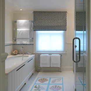 Coastal bathroom in London with a submerged bath, multi-coloured tiles, mosaic tiles and beige walls.