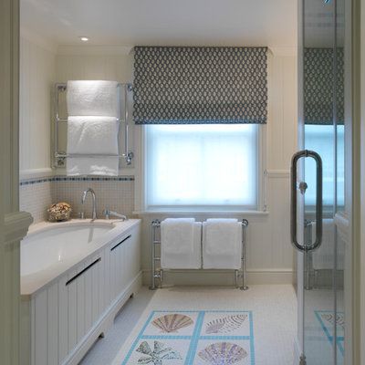 Example of a beach style multicolored tile and mosaic tile bathroom design in London with an undermount tub and beige walls