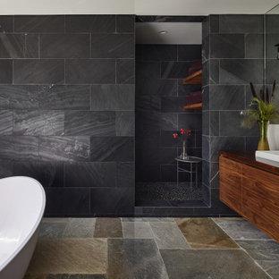 Пример оригинального дизайна: большая главная ванная комната в стиле ретро с фасадами островного типа, коричневыми фасадами, отдельно стоящей ванной, душевой комнатой, унитазом-моноблоком, черной плиткой, плиткой из сланца, белыми стенами, полом из сланца, настольной раковиной, столешницей из дерева, разноцветным полом, открытым душем и коричневой столешницей