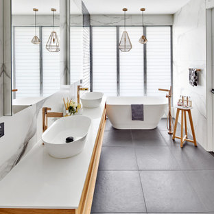 Expansive contemporary master bathroom in Sydney with flat-panel cabinets, beige cabinets, a freestanding tub, gray tile, porcelain tile, porcelain floors, a vessel sink, solid surface benchtops, grey floor and white benchtops.