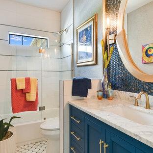 Immagine di una piccola stanza da bagno moderna con ante in stile shaker, ante blu, vasca ad alcova, vasca/doccia, piastrelle blu, piastrelle a mosaico, pavimento con piastrelle in ceramica, lavabo sottopiano, top in marmo, pavimento multicolore, porta doccia a battente e top bianco
