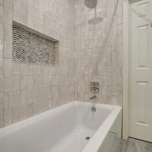На фото: детская ванная комната среднего размера в классическом стиле с фасадами в стиле шейкер, белыми фасадами, ванной в нише, душем над ванной, унитазом-моноблоком, серой плиткой, цементной плиткой, белыми стенами, полом из керамической плитки, накладной раковиной, столешницей из кварцита, серым полом, шторкой для ванной, белой столешницей, нишей, тумбой под одну раковину и встроенной тумбой с
