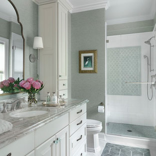 Alcove shower - mid-sized traditional porcelain tile and white tile porcelain tile and white floor alcove shower idea in St Louis with raised-panel cabinets, green walls, an undermount sink, quartzite countertops, a hinged shower door and white cabinets