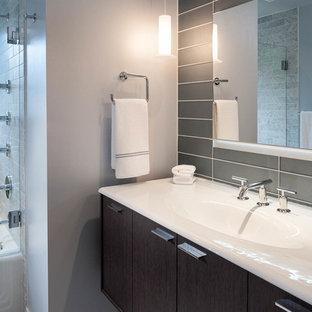 Ispirazione per una stanza da bagno moderna di medie dimensioni con lavabo da incasso, ante marroni, vasca ad alcova, doccia ad angolo, piastrelle grigie, piastrelle di vetro, pareti grigie e pavimento in marmo