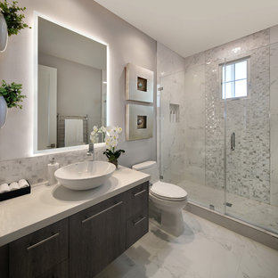 Aménagement d'une petit salle de bain moderne avec un placard à porte plane, des portes de placard en bois sombre, un WC à poser, un carrelage blanc, des carreaux de porcelaine, un mur gris, un sol en carrelage de porcelaine, une vasque, un plan de toilette en quartz modifié, un sol blanc, une cabine de douche à porte battante et un plan de toilette blanc.