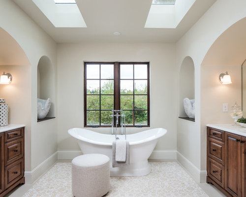 elegant master beige floor freestanding bathtub photo in seattle with raised panel cabinets dark
