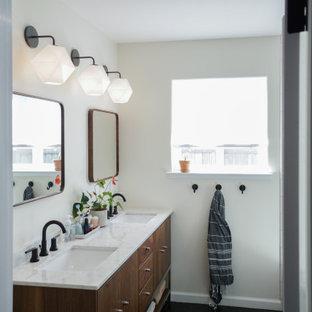 サンフランシスコの中くらいのミッドセンチュリースタイルのおしゃれなマスターバスルーム (中間色木目調キャビネット、一体型トイレ、黄色いタイル、サブウェイタイル、白い壁、セラミックタイルの床、アンダーカウンター洗面器、大理石の洗面台、黒い床、開き戸のシャワー、黄色い洗面カウンター) の写真