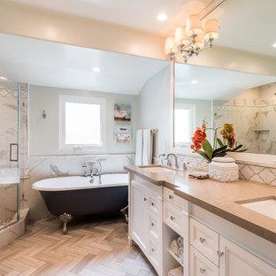 Foto på ett vintage beige badrum, med luckor med infälld panel, vita skåp, ett badkar med tassar, en hörndusch, vit kakel, grå väggar, ett undermonterad handfat, brunt golv och dusch med gångjärnsdörr