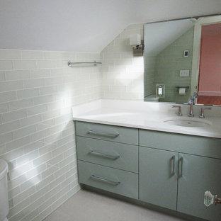 Foto di una stanza da bagno con doccia minimal di medie dimensioni con ante lisce, ante grigie, doccia alcova, piastrelle grigie, piastrelle di vetro, pareti bianche, pavimento in gres porcellanato, lavabo sottopiano, top in superficie solida, pavimento bianco e porta doccia scorrevole