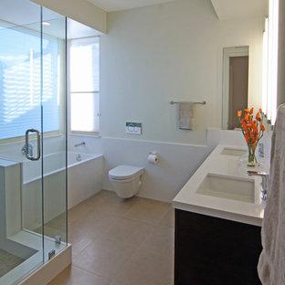 Inspiration för mellanstora moderna en-suite badrum, med ett undermonterad handfat, släta luckor, skåp i mellenmörkt trä, bänkskiva i glas, ett badkar i en alkov, en hörndusch, en vägghängd toalettstol, beige kakel, porslinskakel, gula väggar och klinkergolv i porslin