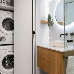 Modelo de cuarto de baño con ducha, contemporáneo, de tamaño medio, con armarios con paneles lisos, puertas de armario de madera oscura, baldosas y/o azulejos grises, paredes blancas, suelo de baldosas de porcelana, lavabo sobreencimera, suelo gris y encimeras blancas